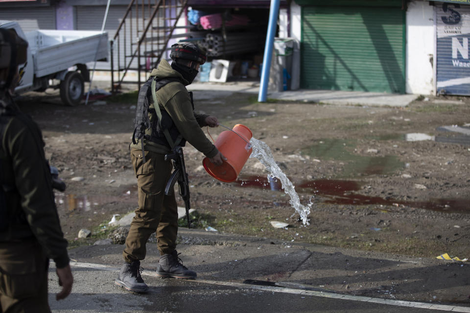 An Indian soldier washes blood stains on a road at the site of an attack on the outskirts of Srinagar, Indian controlled Kashmir, Thursday, March 25, 2021. Rebels fighting against Indian rule in disputed Kashmir Thursday attacked a paramilitary patrol, killing two soldiers and injuring two others, an official said. (AP Photo/Mukhtar Khan)