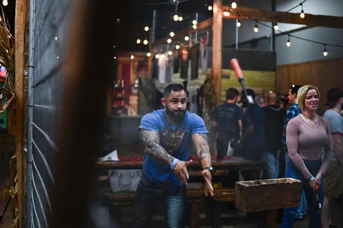 Participants say it takes about a half hour of practice to master the trick of throwing the hatchet so it spins right and sticks in the target, which is replaced several times a day (AFP Photo/Jewel SAMAD)