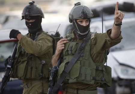An Israeli soldier gestures as he takes part in an operation to locate three Israeli teens near the West Bank City of Hebron
