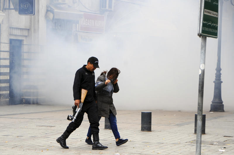 Tunisian policeman escorts a woman away from an area filled with tear gas used by police to break up a protest in Tunis Monday, April 9, 2012. Tunisian policemen clashed with thousands of anti-government protesters who tried to storm Habib Bourguiba Avenue in Tunis on Monday, defying a ban on demonstrations in the area of the revolt that ousted President Zine al-Abidine Ben Ali over a year ago. (AP Photo/Hassene Dridi)