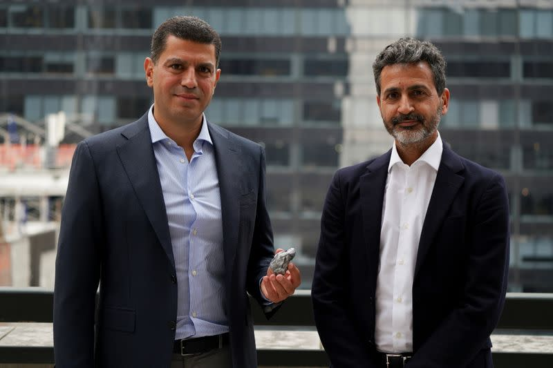 Rafael Papismedov and Oded Mansori pose with an over 1,000-carat uncut stone by Lucara Diamond during a press availability in New York