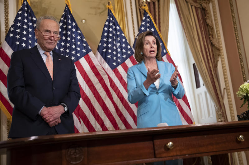 Senate Minority Leader Chuck Schumer, D-N.Y., left, joins Speaker of the House Nancy Pelosi, D-Calif., as she signs the budget package just passed in the Senate to permit the government to resume borrowing to pay all of its obligations and would remove the prospect of a government shutdown in October, at the Capitol in Washington, Thursday, Aug. 1, 2019. (AP Photo/J. Scott Applewhite)