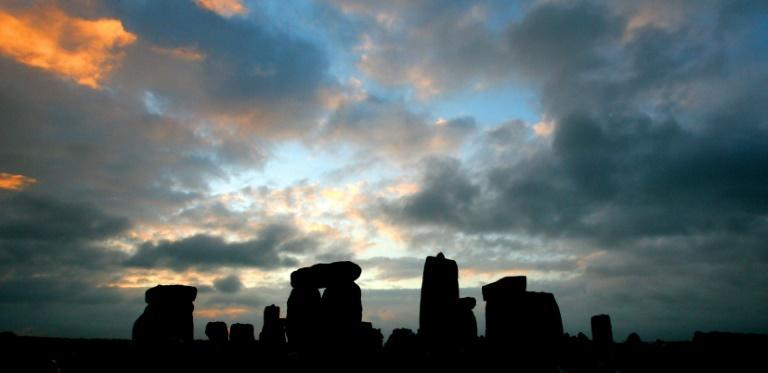 The stone circle of Stonehenge is silhouetted at sunrise during the pagan festival, Summer Solstice, in Avebury, Wiltshire, 21 June 2007