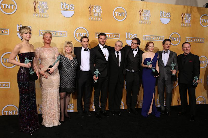 "From left, Jennifer Lawrence, Elisabeth Rohm, Colleen Camp, Alessandro Nivola, Bradley Cooper, Robert De Niro, David O. Russell, Amy Adams, Jeremy Renner and Paul Herman pose in the press room with the award for outstanding performance by a cast in a motion picture for ""American Hustle"" at the 20th annual Screen Actors Guild Awards at the Shrine Auditorium on Saturday, Jan. 18, 2014, in Los Angeles. (Photo by Matt Sayles/Invision/AP)"