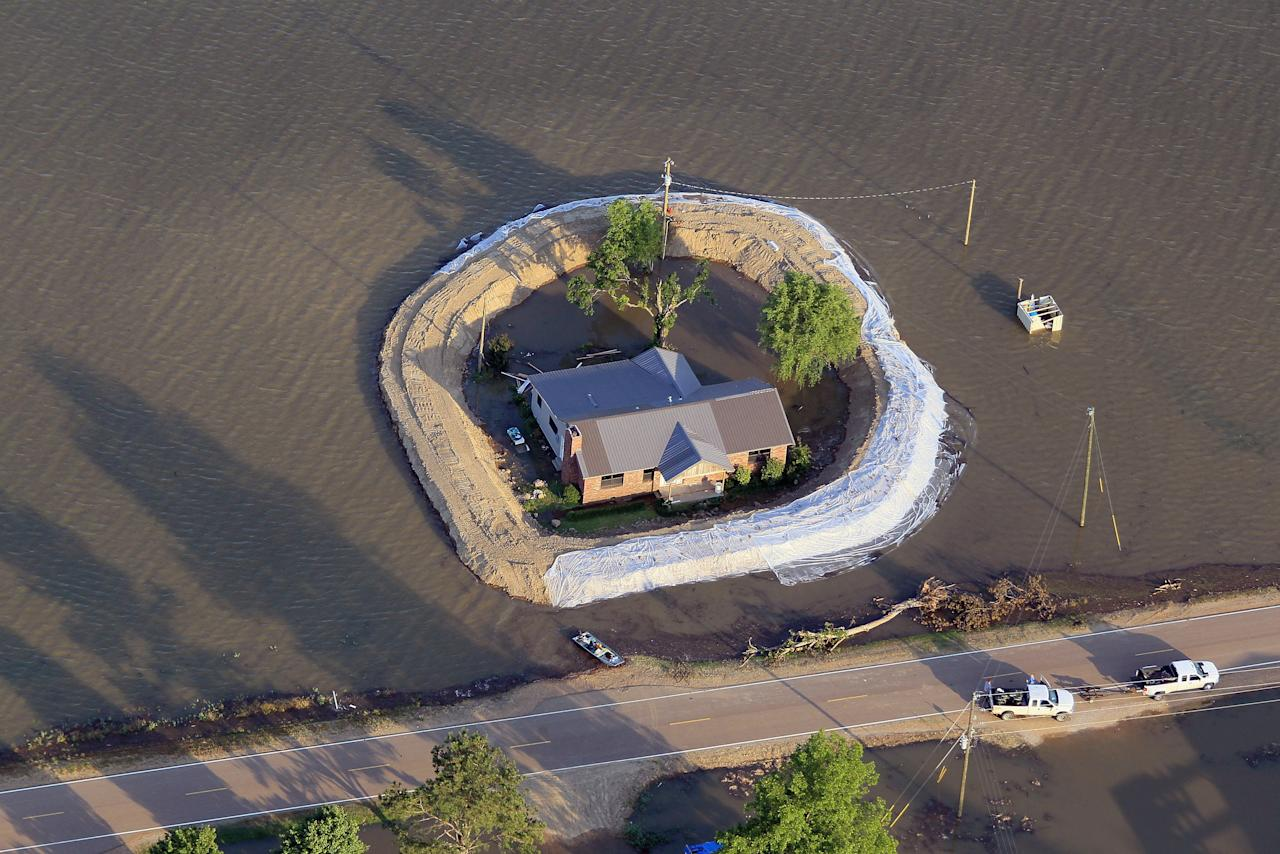 VICKSBURG, MS - MAY 18:  A levee protects a home surrounded by floodwater from the Yazoo River May 18, 2011 near Vicksburg, Mississippi. The flooded Mississippi River is forcing the Yazoo River to top its banks where the two meet near Vicksburg causing towns and farms upstream on the Yazoo to flood. The Mississippi River at Vicksburg is expected to crest May 19. Heavy rains have left the ground saturated, rivers swollen, and have caused widespread flooding along the Mississippi River from Illinois to Louisiana.  (Photo by Scott Olson/Getty Images)