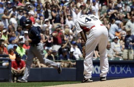 Milwaukee Brewers relief pitcher Alfredo Figaro (45) reacts after giving up a grand slam to Atlanta Braves' Brian McCann during the first inning of a baseball game on Sunday, June 23, 2013, in Milwaukee. (AP Photo/Morry Gash)