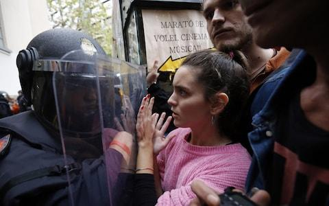 Spanish police push people with a shield outside a polling station in Barcelona - Credit: PAU BARRENA/AFP/Getty Images