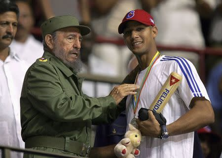 Cuban President Fidel Castro (L) hands out a baseball bat to Cuban player Yulieski Gourriel in Havana in this March 21, 2006 file photograph. REUTERS/Claudia Daut/Files