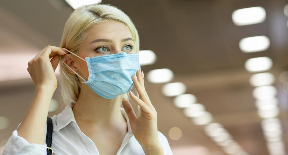 A woman wears a medical mask in shopping centre.