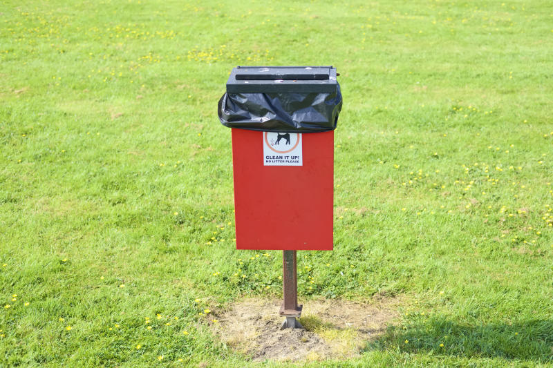 Dog poo waste bin bag environment sign on red bin in public park encouraging owners pick up afterwards uk