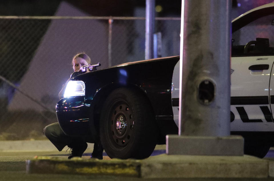 <p>A police officer takes cover behind a police vehicle during the shooting. (AP Photo/John Locher) </p>