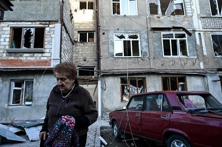 An elderly woman carrying her belongings walks away from an apartment building that was allegedly damaged by recent shelling in the breakaway Nagorno-Karabakh region's main city of Stepanakert