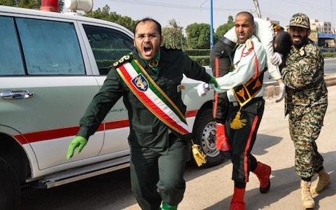 <span>Iranian soldier carrying an injured comrade at the scene of an attack on a military parade in the southwestern city of Ahvaz</span> <span>Credit: AFP </span>
