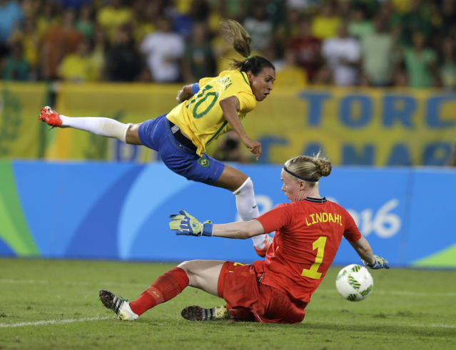 FILE - In this Aug. 6, 2016, file photo, Brazil's Marta, left, leaps over Sweden goalkeeper Hedvig Lindahl as she attempts a shot on goal during the Olympic soccer tournament in Rio De Janeiro, Brazil. The Women's World Cup kicks off Friday, June 7, 2019, in Paris. Marta Vieira da Silva, known by just her first name, is a six-time FIFA World Player of the Year. The 33-year-old has the most World Cup goals among women with 15. (AP Photo/Leo Correa, File)