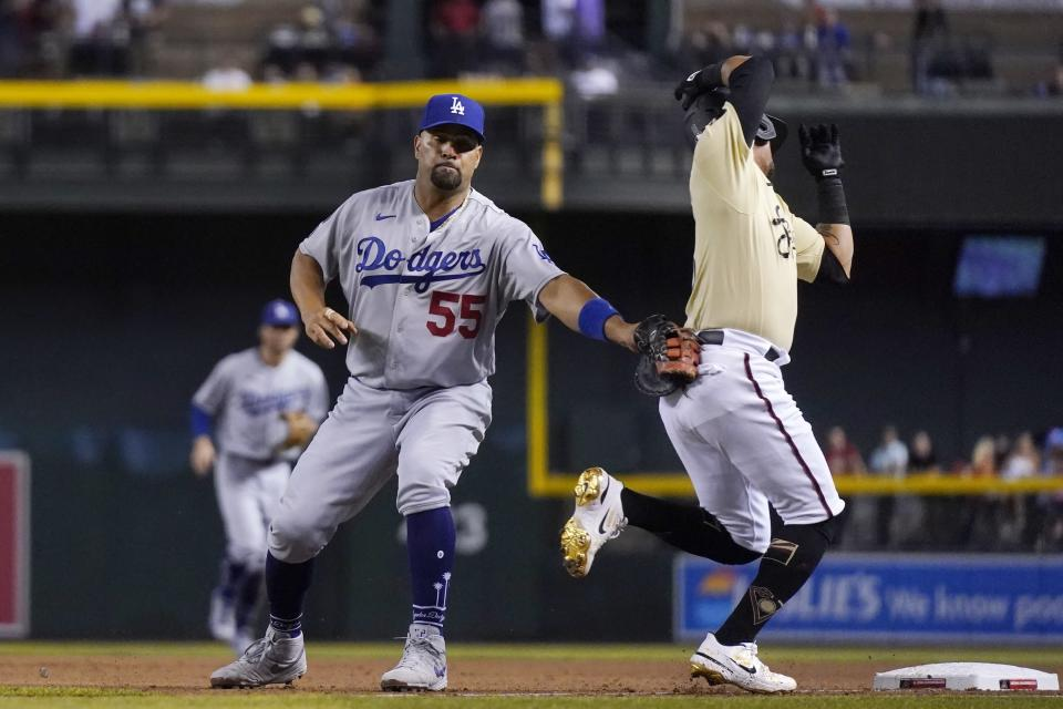 Los Angeles Dodgers first baseman Albert Pujols (55) tags out Arizona Diamondbacks' Ildemaro Vargas as a wide throw took Pujols off the base during the seventh inning of a baseball game Friday, June 18, 2021, in Phoenix. (AP Photo/Ross D. Franklin)