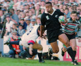 FILE - In this June 18, 1995 file photo, New Zealand All Blacks winger Jonah Lomu runs around England's Will Carling on his way to score the opening try in the Rugby World Cup semifinal at Newlands in Cape Town, South Africa. One trampling run launched Jonah Lomu to global stardom and ensured his name will be indelibly linked to a Rugby World Cup semifinal between New Zealand and England. The All Blacks wingers rampaging runs during that era-defining World Cup in South Africa in 1995 were highlighted by his four-try haul against England in the semifinals. New Zealand and England meet again in the semifinals this Saturday, Oct. 26, 2019, at Yokohama. (AP Photo/Ross Setford, File)