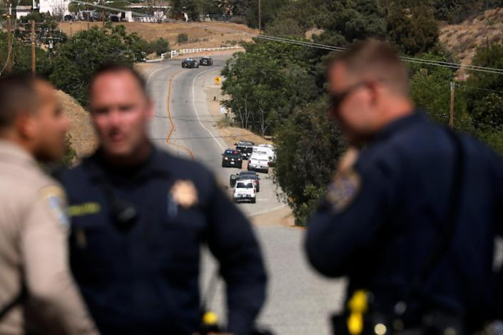 Law enforcement authorities close off a road on Tuesday during an investigation after a shooting at a Los Angeles County Fire Department station near Santa Clarita, California.