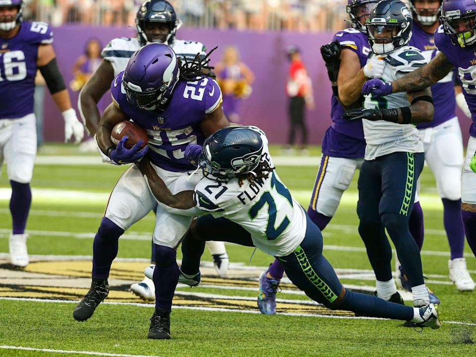Alexander Mattison fights through a tackle against the Seattle Seahawks.