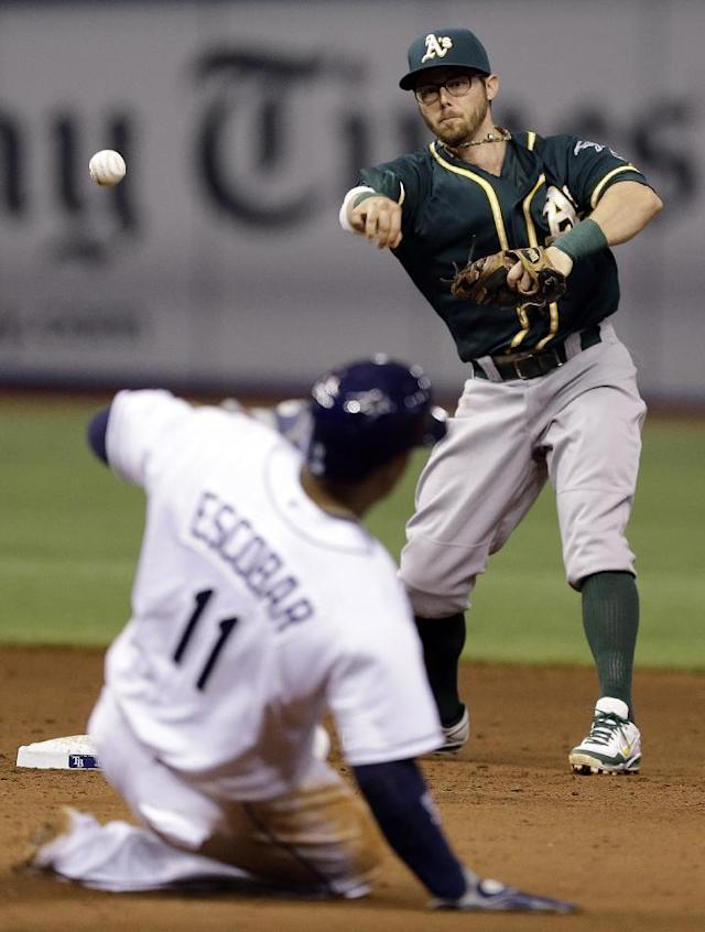 Oakland Athletics second baseman Eric Sogard throws to first after forcing out Tampa Bay Rays' Yunel Escobar (11) at second base during the fifth inning of a baseball game Tuesday, May 20, 2014, in St. Petersburg, Fla. Jose Molina was out at first. (AP Photo/Chris O'Meara)
