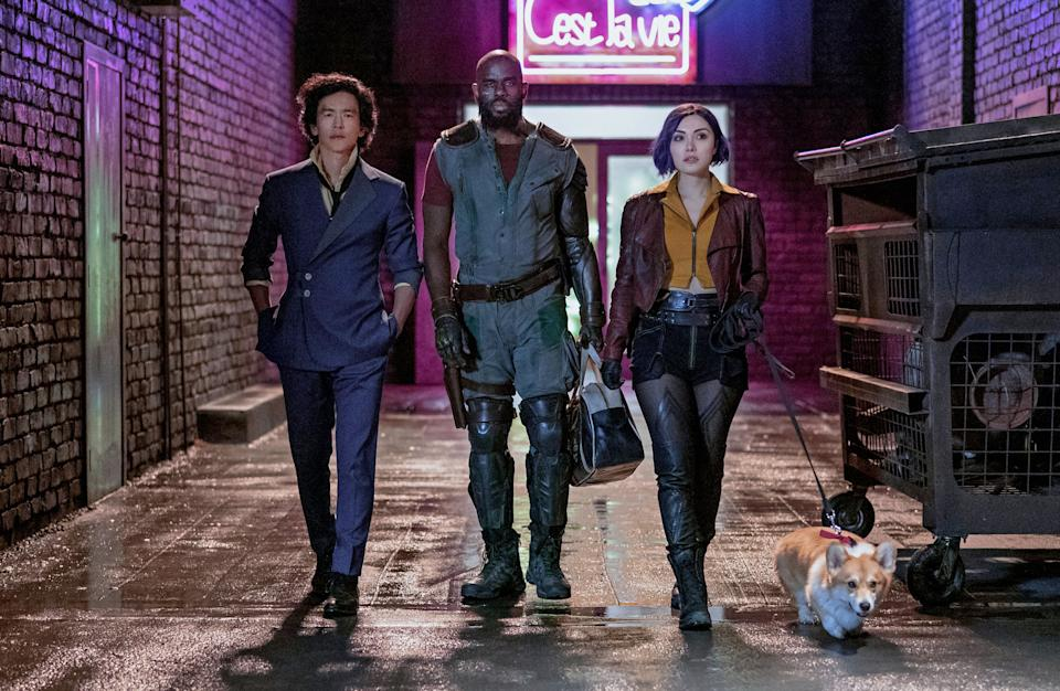 A still promoting the new live-action Netflix series 'Cowboy Bebop' showing three people and a corgi walking down a water-slicked back alley.