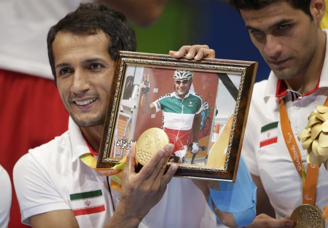 2016 Rio Paralympics - Sitting Volleyball - Victory Ceremony - Men's Gold Medal Match - Riocentro Pavilion 6 - Rio de Janeiro, Brazil - 18/09/2016. Ramezan Salehihajikolaei (IRI) of Iran holds his gold medal and a photograph of Iranian cyclist Sarafraz Bahman Golbarnezhad, during the medal ceremony. REUTERS/Ueslei Marcelino FOR EDITORIAL USE ONLY. NOT FOR SALE FOR MARKETING OR ADVERTISING CAMPAIGNS.