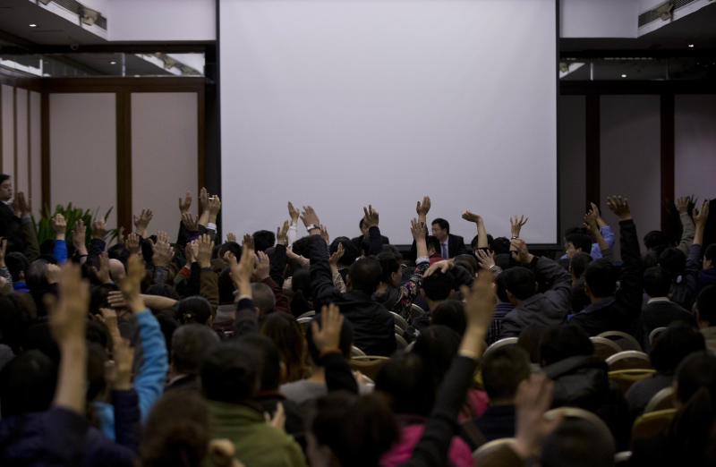 Relatives of Chinese passengers aboard the missing Malaysia Airlines Flight MH370 raise their hands to question Malaysian government officials during a news briefing held by the airlines at a hotel ballroom in Beijing Monday, March 17, 2014. The search for the missing Malaysian jet pushed deep into the northern and southern hemispheres Monday as Australia took the lead in scouring the seas of the southern Indian Ocean and Kazakhstan - about 10,000 miles to the northwest - answered Malaysia's call for help in the unprecedented hunt. (AP Photo/Andy Wong)