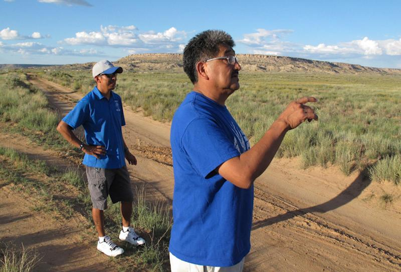 In this Friday, Oct. 13, 2013 photo, Juwan Nuvayokva, assistant coach for the Hopi High School boys cross-country team, left, and head coach Rick Baker await the return of the team from a practice run near Polacca, Ariz. Hopi High School has earned 23 state cross-country titles in a row. But this is not only about sports. This is about the enduring spirit of a culture, where running is rooted in this tribe's tradition. (AP Photo/Felicia Fonseca)