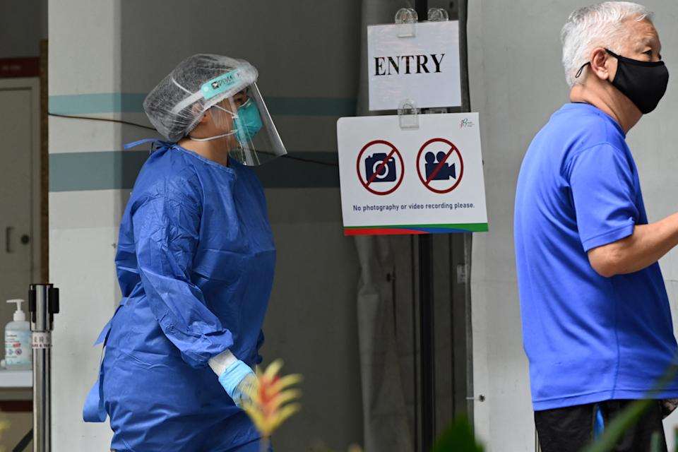 A health staff member dressed in personal protective equipment (PPE) prepares to get samples from residents at a temporary swab centre set up at the void deck area on the ground floor of a public housing block, after a few positive Covid-19 coronavirus cases were detected in the building, in Singapore on May 21, 2021. (Photo by Roslan RAHMAN / AFP) (Photo by ROSLAN RAHMAN/AFP via Getty Images)