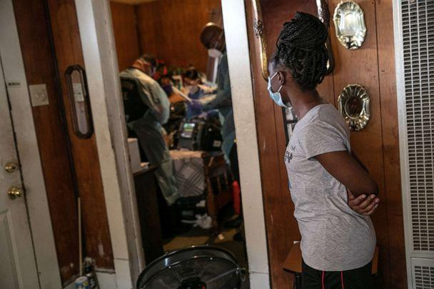 PHOTO: A girl watches as medics treat her grandmother suffering from possible COVID-19, Aug. 12, 2020, in Houston, Texas. (John Moore/Getty Images, FILE)