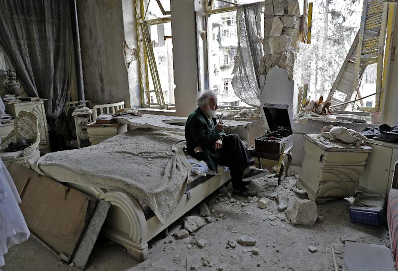 Mohammed Mohiedin Anis, 70, smokes his pipe as he sits in his destroyed bedroom listening to music on his vinyl player in Aleppo's formerly rebel-held al-Shaar neighbourhood (AFP Photo/JOSEPH EID)