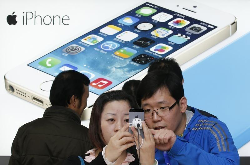 A staff of a China Mobile shop (R) explains a function of the iPhone 5s to a customer in Beijing