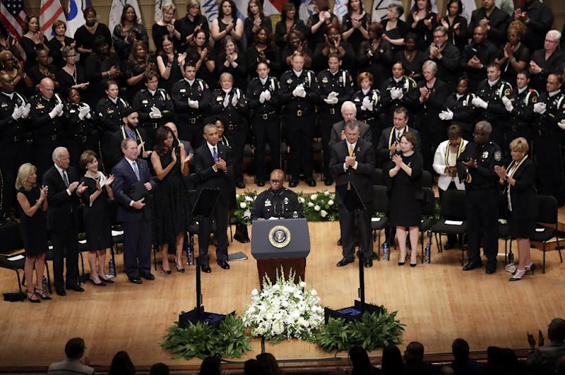FILE - In this July 12, 2016, file photo, Dallas Police Chief David Brown, at podium, speaks as President Barack Obama, former president George W. Bush and Vice President Joe Biden along with others stand and applaud during a memorial service for five police officers that were killed, at the Morton H. Meyerson Symphony Center in Dallas. The now retired Dallas Police Chief, who stepped into the national spotlight after a sniper killed five law enforcement officers at a July protest in Dallas, will step back into the spotlight as a contributor for ABC News, according to a news release posted on ABC News' website Wednesday, Nov. 30, 2016. (AP Photo/Eric Gay, File)