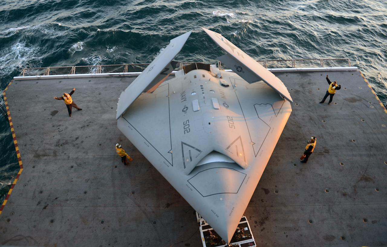 ATLANTIC OCEAN - MAY 14:  In this handout released by the U.S. Navy, Sailors move an X-47B Unmanned Combat Air System (UCAS) demonstrator onto an aircraft elevator aboard the aircraft carrier USS George H.W. Bush (CVN 77) May 14, 2013 in the Atlantic Ocean. George H.W. Bush is scheduled to be the first aircraft carrier to catapult-launch an unmanned aircraft from its flight deck. The Navy plans to have unmanned aircraft on each of its carriers to be used for surveillance and be armed and used in combat roles.  (Photo by Mass Communication Specialist 2nd Class Timothy Walter/U.S. Navy via Getty Images)