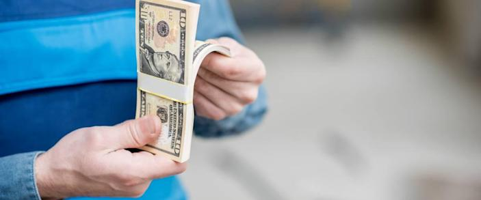 Man in a striped shirt counts pile of cash, close up of hands holding money.