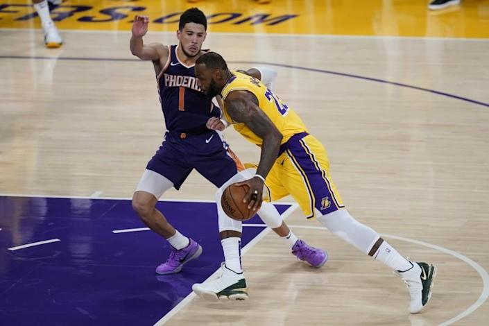 The Lakers' LeBron James drives against the Phoenix Suns' Devin Booker on June 3, 2021.