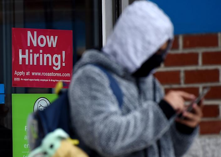 """A man wearing a face mask stands next to a """"Now Hiring """" sign in front of a store in Arlington, Virginia, onDec. 18. (Photo: OLIVIER DOULIERY/AFP via Getty Images)"""