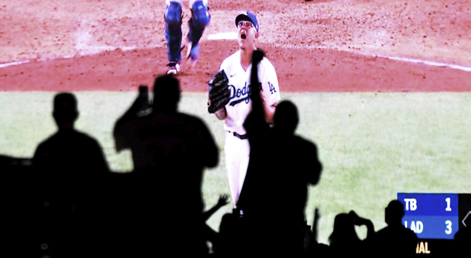 Julio Urias of the Los Angeles Dodgers reacts after the last out as fans celebrate from their cars as they watch the national broadcast of the Los Angeles Dodgers defeat the Tampa Bay Rays 3-1 during game 6 to win the the 2020 MLB World Series baseball game in the parking lot at Dodger Stadium in Los Angeles on Tuesday, October 27, 2020. (Keith Birmingham/The Orange County Register via AP)