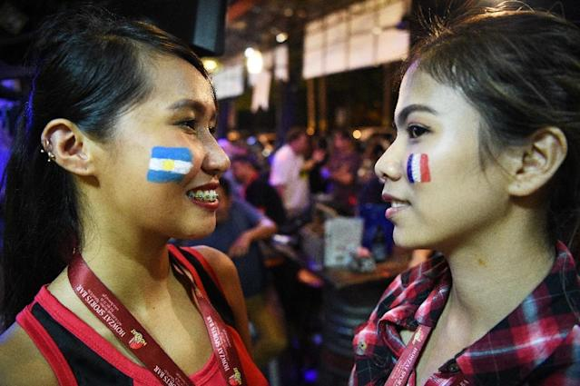 Fever pitch: Manila bar staff have faces painted with the flags of Argentina and France during a World Cup match (AFP Photo/TED ALJIBE)