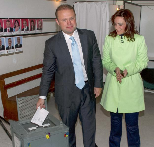 Maltese Labour Party leader Joseph Muscat, casts his ballot as his wife Michelle looks on, in Valletta, Malta, Saturday, March 9, 2013. Maltese head to the polls Saturday to decide whether to grant the center-right Nationalist Party a fourth straight term or give the opposition a shot at government after 15 years. (AP Photo/Lino Arrigo Azzopardi)