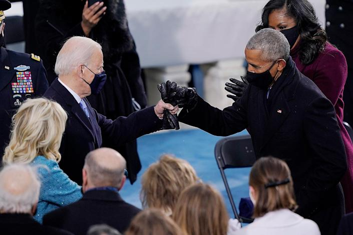 """<p>Before being sworn in as the 46th President of the United States, Joe Biden exchanges a jovial fist bump with Barack Obama, under whom he served as Vice President from 2008-2016, developing <a href=""""https://people.com/politics/joe-biden-and-barack-obama-close-bond-through-the-years/"""" rel=""""nofollow noopener"""" target=""""_blank"""" data-ylk=""""slk:a close bond."""" class=""""link rapid-noclick-resp"""">a close bond.</a></p>"""