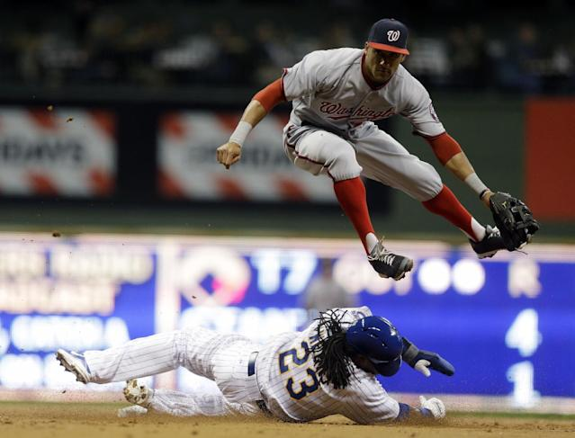 Washington Nationals' Ian Desmond, top, leaps over Milwaukee Brewers' Rickie Weeks (23) to turn a double play on a ball hit by Norichika Aoki during the third inning of a baseball game on Friday, Aug. 2, 2013, in Milwaukee. (AP Photo/Morry Gash)