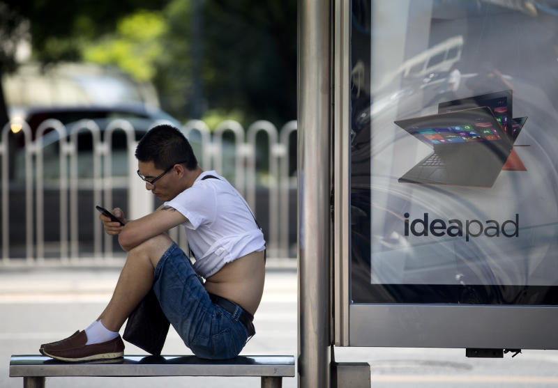 A man checks on his smartphone at a bus stand displaying a tablet computer advertisement in Beijing, China Monday, Aug. 19, 2013. Many famous Chinese - from pop stars to scholars, journalists to business tycoons - have amassed substantial online followings, and these larger-than-life personalities don't always hew to the Communist Party line. Now Beijing is tightening its grip on China's already heavily restricted Internet by making influential microbloggers uncomfortable when they post material the government doesn't like. (AP Photo/Andy Wong)