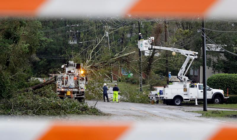 Duke Energy employees work on removing trees and restoring power to a road closed in Wilmington, N.C., after Hurricane Florence traveled through the area Sunday, Sept. 16, 2018. (AP Photo/Chuck Burton)