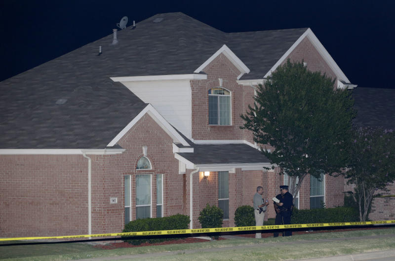 A law enforcement officers confer outside the house of a fatal shooting early Thursday morning, Aug. 8, 2013, in DeSoto, Texas. Four people were killed at two different locations in South Dallas County and the suspected shooter is in police custody. (AP Photo/LM Otero)
