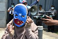 Indonesian student activists take part in a role-play as they demonstrate against alleged human rights abuses of China's Uyghur minority Muslim group, outside the Chinese embassy in Jakarta