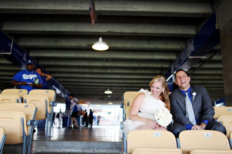 "This July 4, 2011 photo released by Adrienne Gunde Photography shows Holly and Jeff Lowzik at their wedding held at Dodgers Stadium in Los Angeles. Some couples, find that the massive stadiums where they enjoy hearing the crack of the bat can also be the perfect place to hear their beloved say, ""I do."" (AP Photo/Adrienne Gunde Photography)"