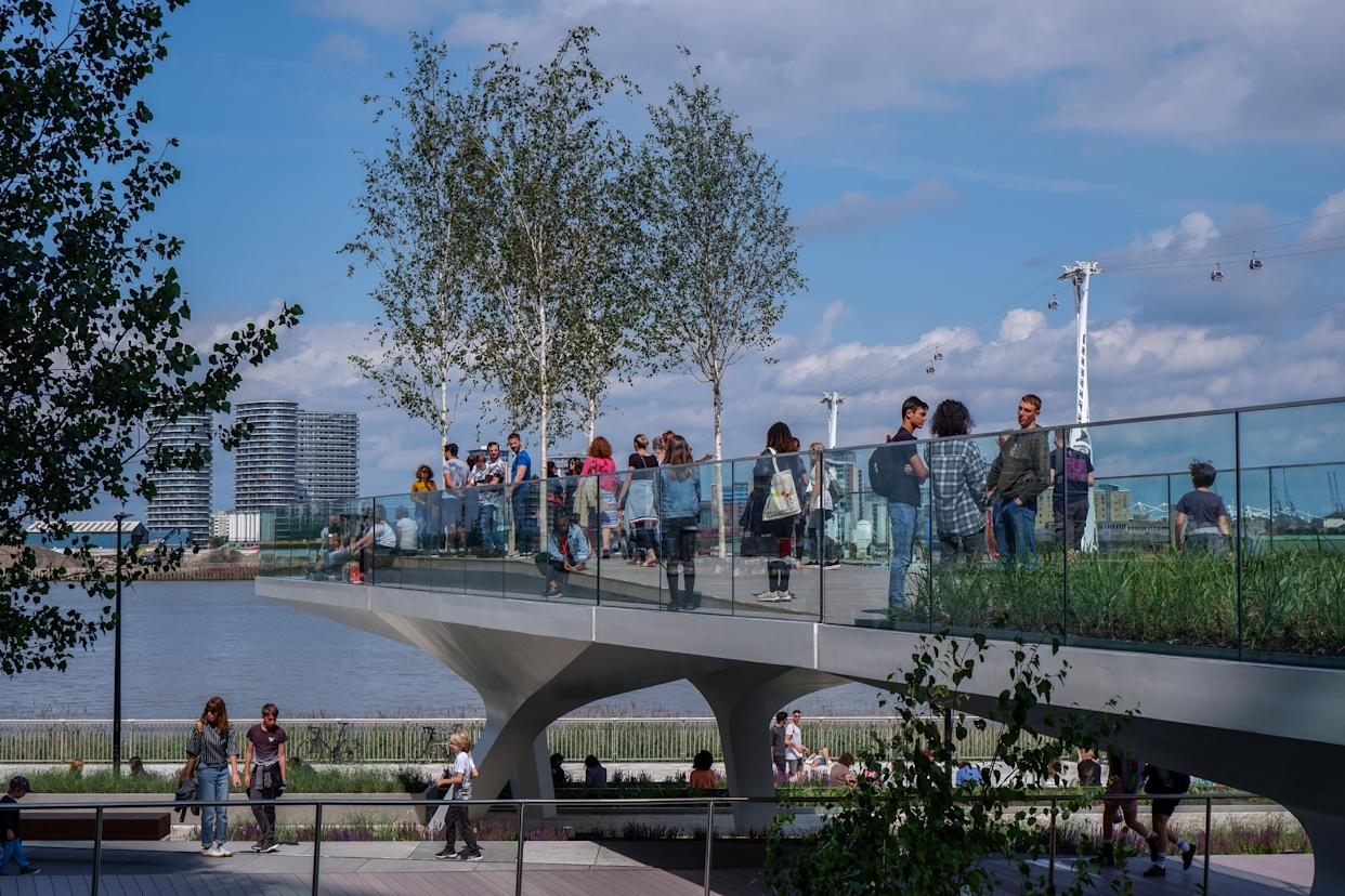People walking 'The Tide' bridges . The Tide is a linear park with elevated walks around the Greenwich Peninsula South London England UK