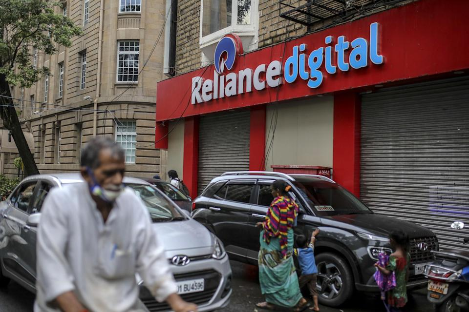 Pedestrians walk past a store of Reliance Digital Retail Ltd., a subsidiary of Reliance Industries Ltd., in Mumbai, India, on Tuesday, July 14, 2020. Google is in advanced talks to buy a $4 billion stake in Jio Platforms Ltd., the digital arm of Indian billionaire Mukesh Ambani's conglomerate, people familiar with the matter said, seeking to join rival Facebook Inc. in chasing growth in a promising internet and e-commerce market. Photographer: Dhiraj Singh/Bloomberg via Getty Images