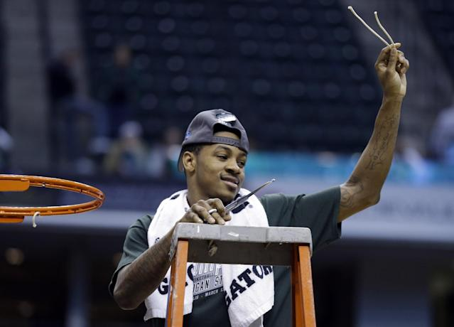 Michigan State guard Keith Appling holds up pieces of the net after his team defeated Michigan 69-55 in an NCAA college basketball game in the championship of the Big Ten Conference tournament on Sunday, March 16, 2014, in Indianapolis. (AP Photo/Michael Conroy)