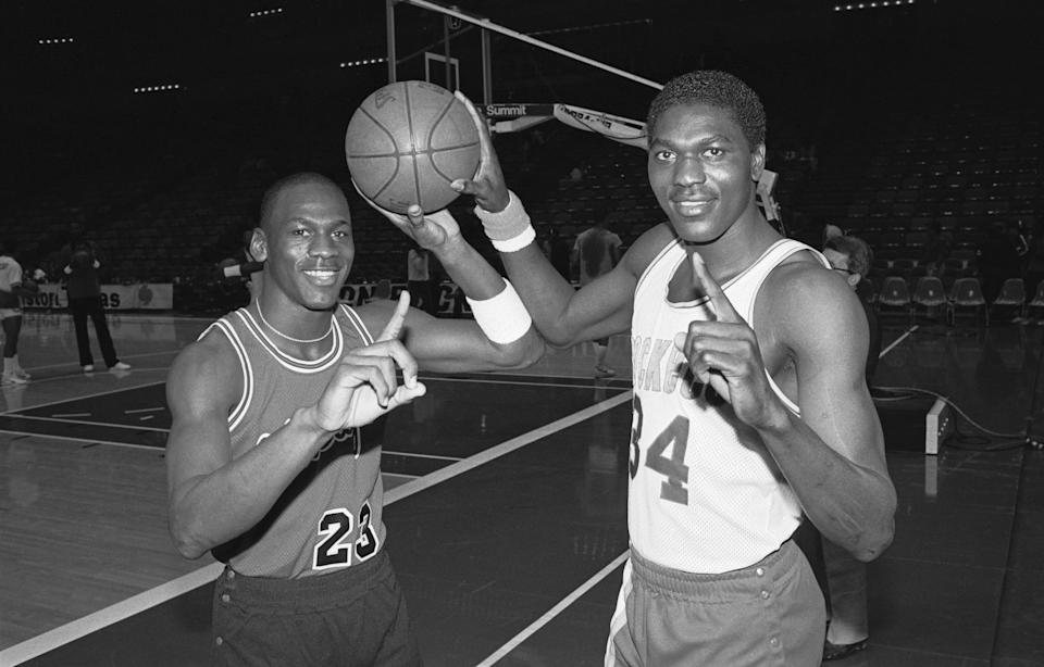 Basketball players with the No. 1 sign holding a basketball on a court.